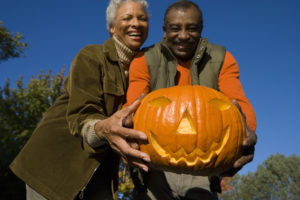 Elderly couple holding a jack-o-lantern